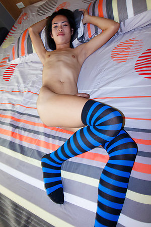 Sexy little Lee is bathed in sunlight by the window wearing a long t-shirt, panties, and blue striped socks.