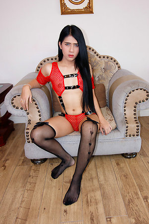 Ladyboy Bipor is wearing red netted fantasy wear held together with black vinyl straps.