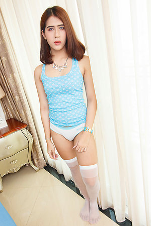 Ladyboy Bipor is by the window wearing a blue tanktop, panties, and white stockings.