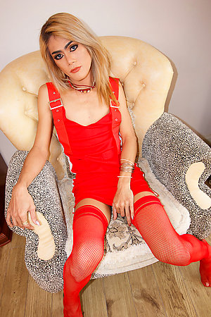 Hard-bodied Num is dressed all in red with a dress, stockings, and a choker.