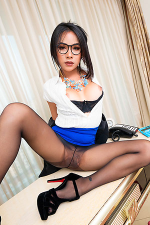 Ladyboy Tata is working on her laptop at her desk, wearing a blazer, white blouse, and skirt with pantyhose and heels.